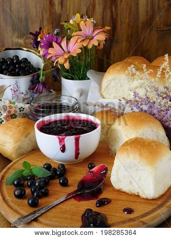 Berry jam in a ceramic bowl, golden buns and a spoon covered with jam