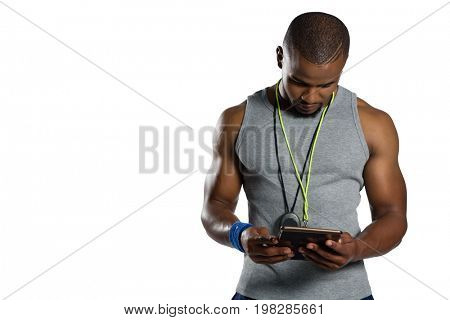 Male rugby instructor using digital tablet while standing against white background