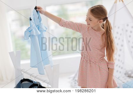 Daily routine of a real fashionista. Cheerful girl beaming while looking at a baby blue shirt and choosing her attire for today.