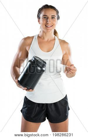 Portrait of happy female athlete taking supplement powder while standing against white background