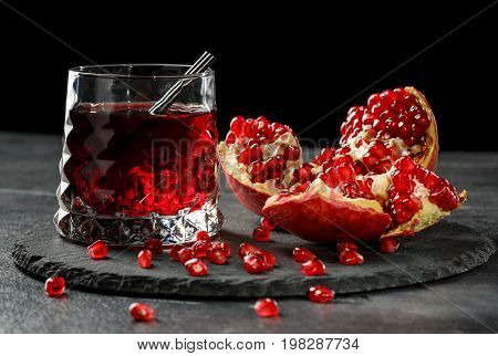A red berry cocktail with a black straw and a part of a pomegranate on a black background. Non-alcohol antioxidant beverage. A grain of bittersweet garnet.  Expensive delicacy drinks for gourmets.