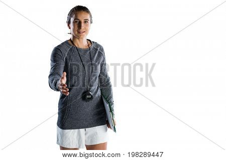 Portrait of confident female rugby coach extending arm for handshake while standing against white backgrond