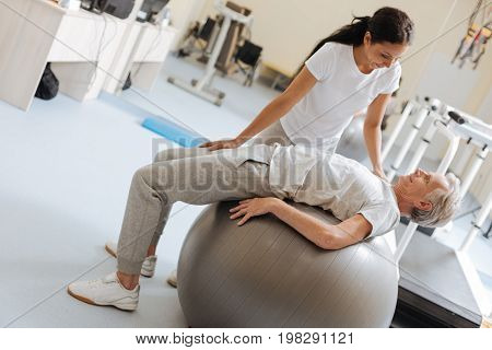 Stretch your back. Smiling pensioner leaning on fitness ball and being in sport clothes while looking at his coach