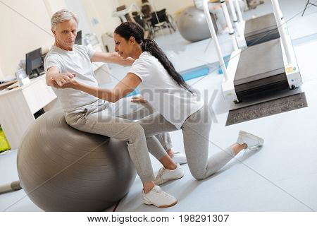 Try to concentrate. Attentive man sitting on big fitness ball and wrinkling forehead while raising both arms