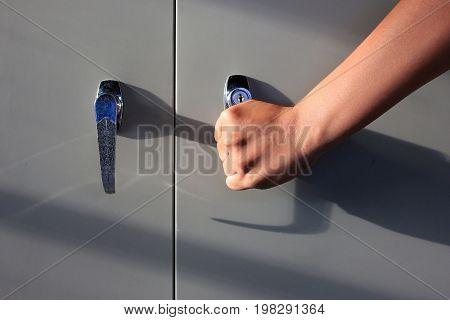 The hand is opening the file cabinet in the office.