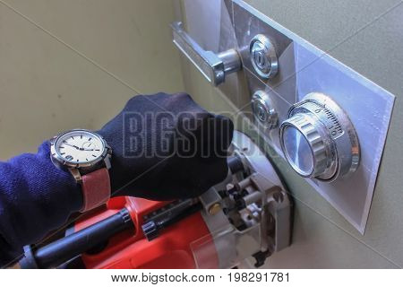 Robber equipment tools stealing a safety deposit box.