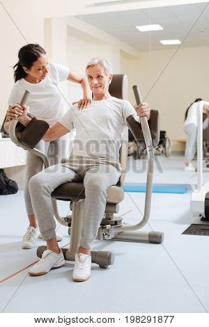 Do not disturb me. Smiling senior man wrinkling forehead while looking forward and doing exercises on training device