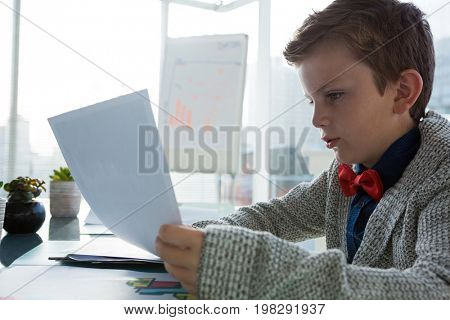 Boy as business executive verifying document in office