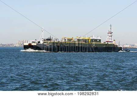 New York City USA - February 1 2009: Tug pushing barge across New York harbor