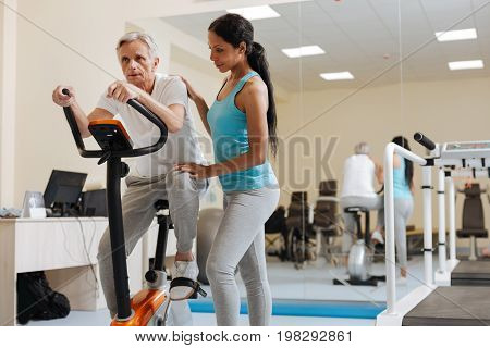 Visit gym. Concentrated pensioner pressing lips and wrinkling forehead while training on simulator