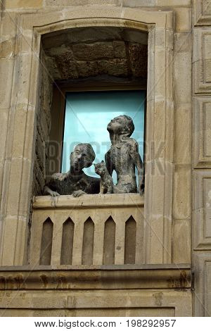 Baku, Azerbaijan - July 23, 2017.  Sculpture of a girl, a boy and a cat looking out of a window in Old Town quarter of Baku.