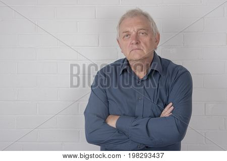 Annoyed mature man standing against a white brick background and copy space