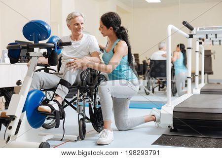 Have a pause. Happy invalid pensioner keeping smile on his face and doing exercise on trainer apparatus