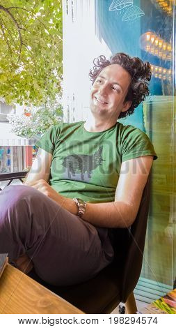 Young Caucasian Cheerful Man With Curly Hair Sitting Happily In A Cafe
