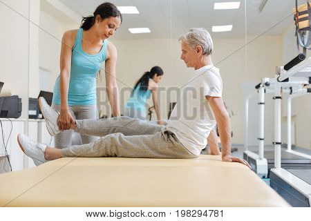 Good support. Delighted foreign female that working in the gym and doing tasks for legs while looking downwards