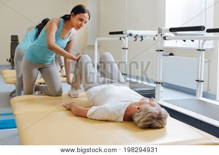 Should have a rest. Attentive brunette leaning his knee on the bed and putting her hand on the knee of her patient while explaining the task