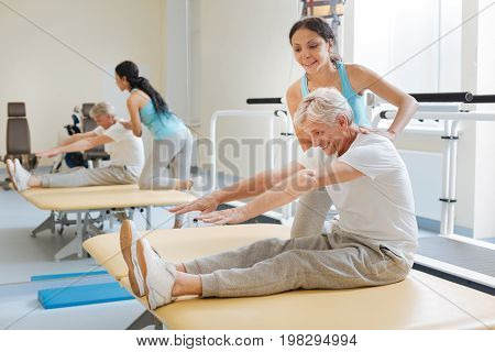 Show your result. Handsome man keeping smile on his face and sitting on the mat while going to touch his feet