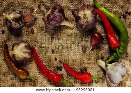 Chili garlic rosemary pepper in the form of a frame on sacking top view