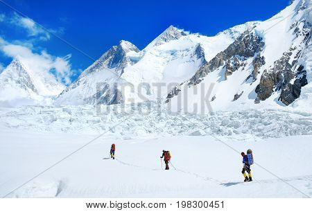 Group Of Climbers With Backpacks Reaches The Summit Of Mountain Peak. Success, Freedom And Happiness