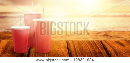 Red cups over white background against view of beach during sunset