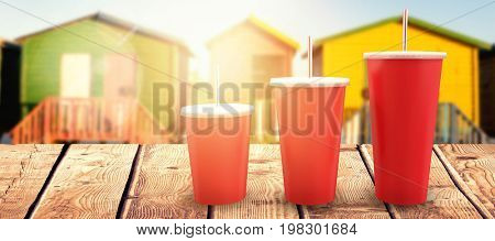 Red cups over white background against multi colored huts on sand against clear sky