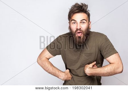 Portrait of funny crazy bearded man with tongue out and dark green t shirt against light gray background. studio shot.