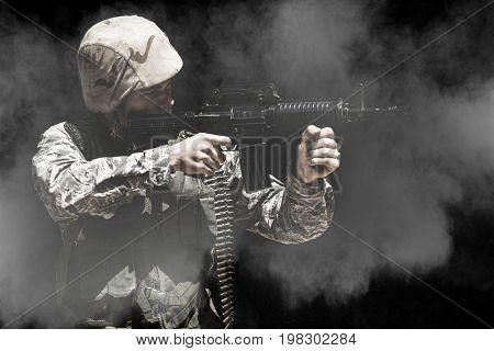 Black background against military soldier aiming with a rifle