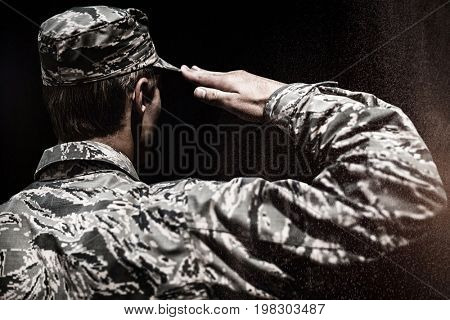Black background against rear view of a military soldier saluting