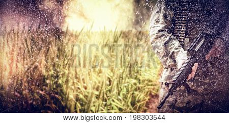 Empty path passing through fields against mid section of military soldier standing with a rifle