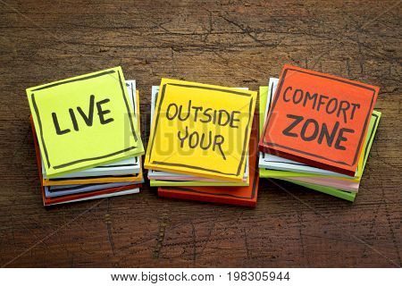 Live outside your comfort zone - motivational handwriting in black ink on sticky notes against rustic wood