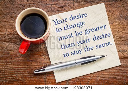 Your desire to change must be greater than your desire to stay the same - inspirational handwriting on a a napkin with a cup of coffee