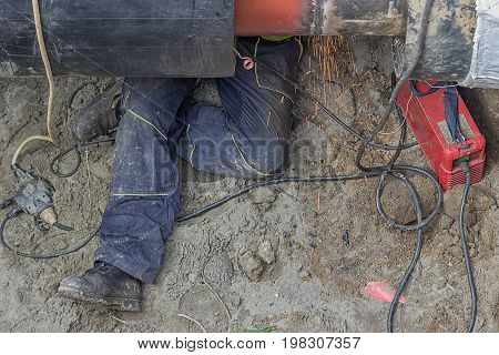 Welder Worker Grinding The Weld In Trench Under Pipeline 2