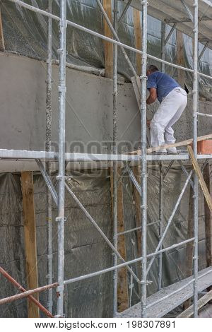 Worker Spreading Mortar On Wall