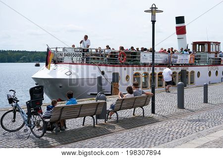 WAREN, GERMANY - JUNE 27, 2017: Pleasure boat in the port of Waren at the Mueritz lake. Many tourists take the opportunity to take a trip on the largest lake in Germany