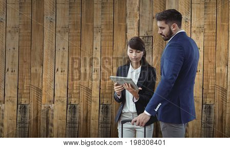 Business colleagues using digital tablet against wooden wall background