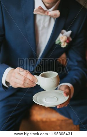 The groom is sitting in a blue suit with a bow tie, holding a white cup and saucer in his hands and drinking coffee.