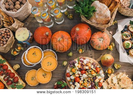 Pie with cherry tomatoes, pumpkin pie, Sun dried tomatoes, Physalis, paper bag with nuts, Basket with bread, lemonade, meat sliced, cookies, pancakes on a wooden table. Top view