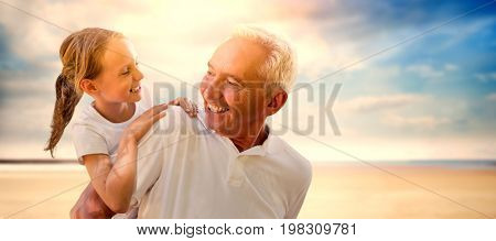 Grandfather holding his grandchild on his back against serene beach landscape