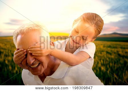Grand child covering grandfathers eyes  against scenic view of wheat field