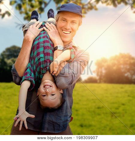 father holding his son upside down against green field against a green forest ans blue sky