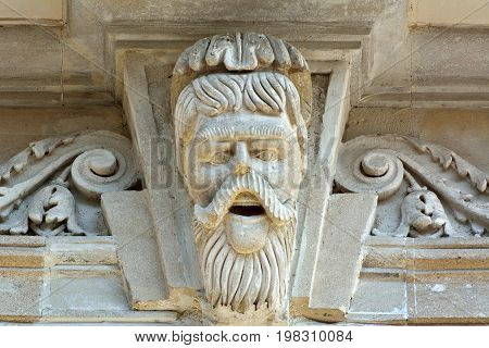 Baku, Azerbaijan - July 23, 2017.  Sculpture of moustached man on facade of architectural building in downtown Baku.