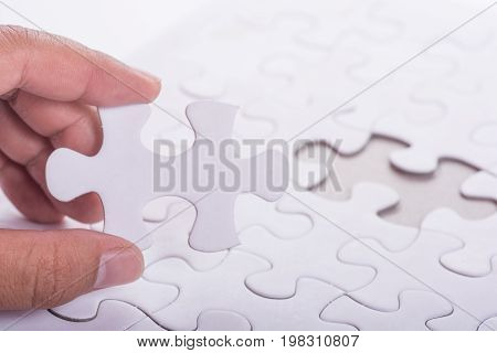 Person's hand completing last piece of Jigsaw puzzles
