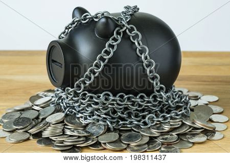 black piggy bank with chains on top of coins as security protection or financial saving concept.