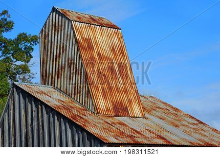 Rustic roof of the Ozark Diamond Mine's historic shaft house is framed by blue sky at the Crater of Diamonds State Park in Arkansas.