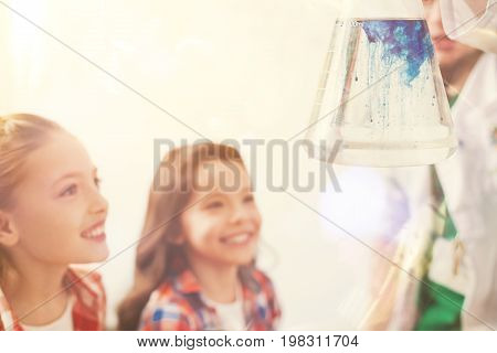 Enter into a reaction. Silhouettes of two girls that standing in semi position and keeping smile on faces while looking upwards