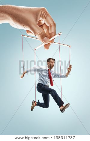 Conceptual image of businessman puppet on gray background