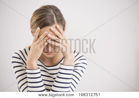 Young hopeless woman suffering from depression having nervous breakdown holding her head on isolated background copy space