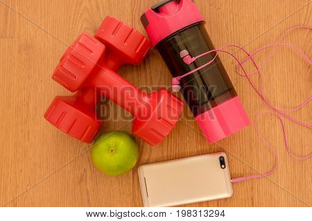 Athlete's set with two pink dumbbells, smarphone with pink headphones, green appple and bottle of water on wooden background.