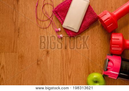 Athlete's set with two pink dumbbells, smarphone with pink headphones over a pink towel, green appple and bottle of water on wooden background.