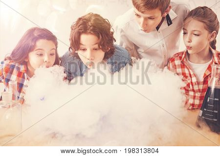 Good job. All pupils standing next to each other and looking forward while blowing on smoke